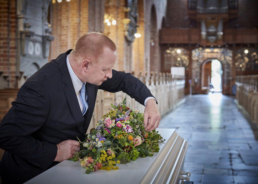 Bedemand pynter kiste i kirke
